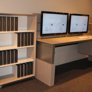 Bookcase and desk with workwall supporting 2 mounted monitors from Creative Wood's 3x9 office casegood collection
